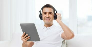 Smiling man with tablet pc and headphones