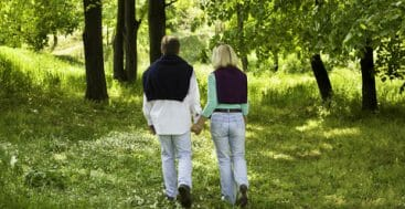 couple walking away in forest